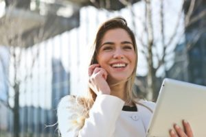 Best Times to Look For a Job - Smiling Woman on Cell Phone Holding Tablet